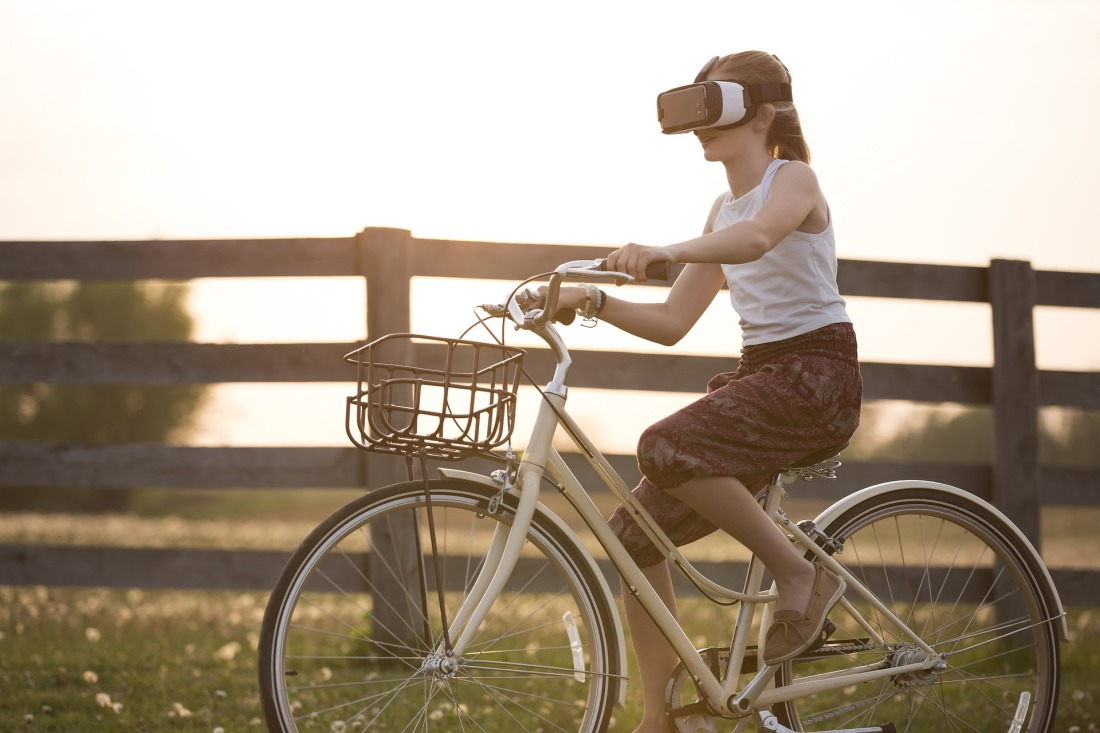Girl riding bike with VR headset on